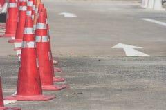 Rad av orange trafikkottar som ställer in på körbanan bredvid parkeringsplats Fotografering för Bildbyråer