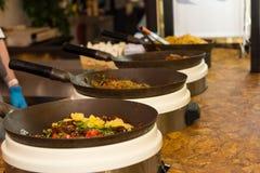 Rad av pannor med lagad mat mat som vilar på en tabell Royaltyfri Foto