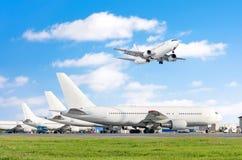Rad av passagerarflygplan, flygplan som parkeras på service för avvikelse på flygplatsen skjuter annat plant tillbaka släp En som Arkivbilder