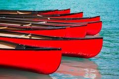 Rad av röda kanoter i sjön Arkivfoton