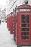 Rad av röda telefonaskar i London Arkivbilder