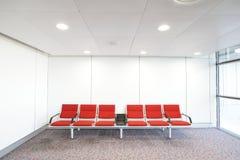 Rad av röd stol på flygplatsen Arkivfoton