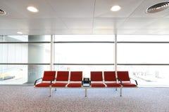 Rad av röd stol på flygplatsen Arkivbilder