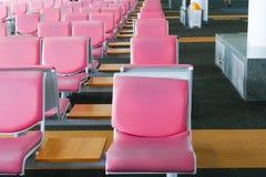 Rad av rosa läderstol på flygplatsen Arkivfoton