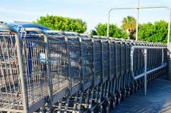 Rad av shoppingvagnar i utomhus- återgång station Arkivbild
