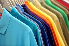Rad av skjortor för polo för man` s i garderob eller lager arkivbilder