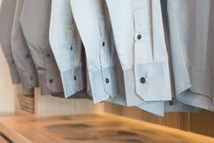 Rad av skjortor som hänger på kuggen med knappar Royaltyfri Foto