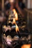 Rad av stearinljus i buddistisk tempel Arkivbilder