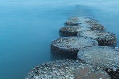 Rad av stenar som kliver på havet Arkivfoton