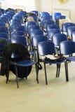 Rad av stolar som står i linje i det tomma rummet Arkivfoton
