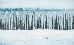 Rad av stora frostiga istappar i natur Rad av stora frostiga istappar i natur Istappbakgrund Royaltyfri Bild
