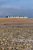 Rad av strandkojor som stångar stranden Arkivfoton
