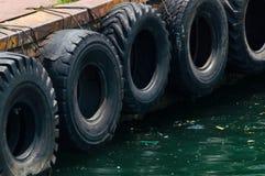 Rad av svarta bilgummihjul som används som fartygstötdämpare Royaltyfri Foto