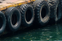 Rad av svarta bilgummihjul som används som fartygstötdämpare Arkivbild