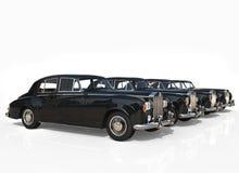 Rad av svarta tappningbilar på vit bakgrund Royaltyfria Bilder