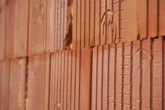 Rad av tegelstenar i röd färg med de inre hålen i formen av honungskakan på konstruktionsplatsen Arkivfoto