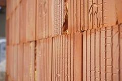 Rad av tegelstenar i röd färg med de inre hålen i formen av honungskakan på konstruktionsplatsen Arkivbild