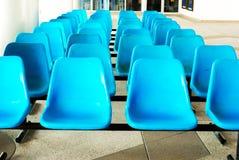 Rad av tomma blåa plast-stolar/den tomma blåttplatsen royaltyfria foton