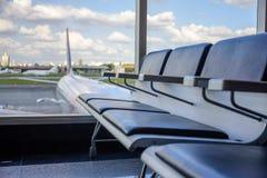 Rad av tomma svarta läderplatser i väntande vardagsrum på flygplatsen Royaltyfri Fotografi