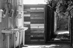 Rad av trästugan på bygd med rad av den keramiska vasken för whit i förgrund Royaltyfri Foto