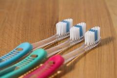 Rad av tre nya tandborstar Arkivbilder