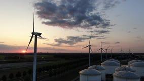 Rad av väderkvarnar som frambringar grön elektricitet på solnedgången i industriellt hamnområde med silor arkivfilmer