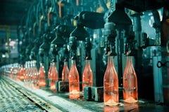 Rad av varma orange glasflaskor