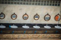 Rad av vita tvättställar i badrummet med rad av speglar in Arkivfoton