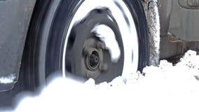 Rad eines Autos dreht sich und gleitet im tiefen Schnee stock video footage