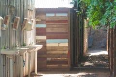 Rad för härlig sikt av trästugan på bygd med rad av den keramiska vasken för whit i förgrund Royaltyfri Fotografi
