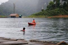 Rad för två broder en kajak i sjön på den Ratchaprapa fördämningen Royaltyfria Bilder