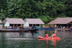 Rad för två broder en kajak i sjön på den Ratchaprapa fördämningen Arkivbild