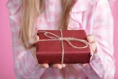 Rad-giftbox in den weiblichen Händen im rosa Hintergrund Lizenzfreie Stockfotografie