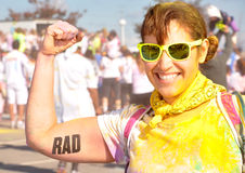 Rad girl in yellow sunglasses. Girl flexing muscles with a Rad tattoo on her arm. She is wearing yellow sunglasses and a yellow bandanna with yellow color powder Stock Images