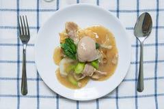 Rad Na,著名泰国中国式宽米线盘用鲜美嫩猪肉用浓小汤调味汁 与匙子叉子的平的位置 免版税库存照片