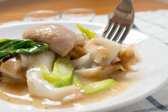 Rad Na,著名泰国中国式宽米线盘用鲜美嫩猪肉用浓小汤调味汁 关闭与叉子 免版税图库摄影