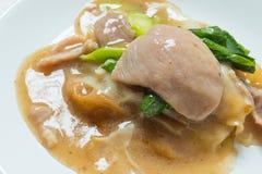Rad Na berömd thailändsk för risnudel för kinesisk stil bred maträtt med smakligt mjukt griskött med tjock skysås close upp fotografering för bildbyråer