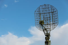 Radar. The antenna of the radar on the background of blue sky with white clouds Royalty Free Stock Photo