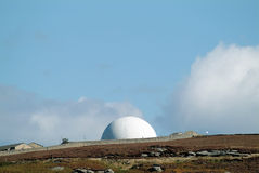 Radar dome. Military radar dome in English countryside, moorland and rocks in foreground, against blue sky with clouds stock photos