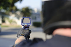 Radar gun. A motorcycle police officer aims his radar gun at the street Royalty Free Stock Photo
