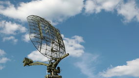 Radar. The rotating antenna of the radar on the background of blue sky with white clouds