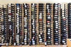 Radda en Chianti, Italia - 20 de abril de 2018: Tenedor con las botellas de vino Tienda de vino del escaparate Pared con las bote imagen de archivo