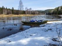 Radeau sur la banque neigeuse de la rivière Transporter de ressort photo stock