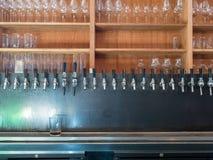 Raden av öl knackar lätt på i baksida av stången med soligt ljus Arkivbild