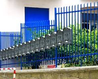 Raden av grå färgmetallbrevlådor near räcket Royaltyfri Fotografi