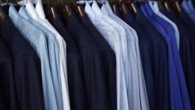 Raden av män passar omslag och skjortor på hängare arkivfilmer