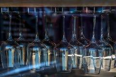 Raden av rent vinexponeringsglas som hänger på den uppochnervända ställningen shoppar in, fönstret Massor av vinexponeringsglas t arkivfoto