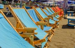 Raden av solstolar på ett soligt värme stranden royaltyfria foton