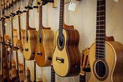 Rader av akustiska gitarrer på väggen arkivbild