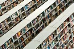 Rader av böcker i ett offentligt bibliotek arkivfoto